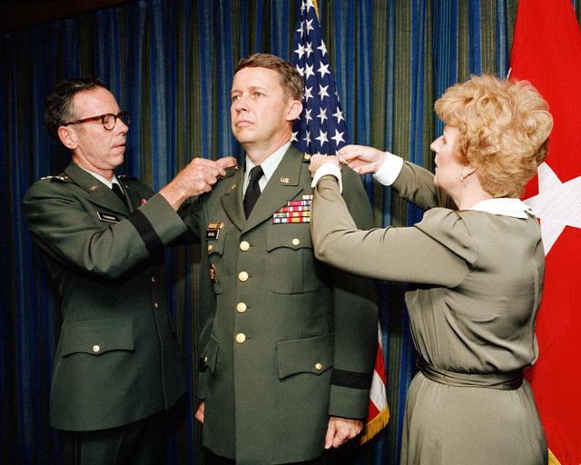 LGEN M.R. Thurman, deputy chief of staff for personnel, pins the stars on BGEN John H. Mitchell, director of Human Resources Development, that promote him to the tank of MGEN. Assisting in the ceremony held at the Pentagon is MGEN Mitchell's wife Joan