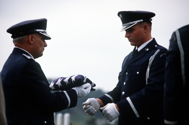 LT. COL. Fash, a Protestant chaplain, receives the flag from SENIOR AIRMAN Hawkins during a funeral ceremony at the Arlington National Cemetery. Fash will present the flag to the family of the deceased