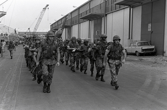 Marines from the 32nd Marine Amphibious Unit walk down the pier after leaving the tank landing ship USS MANITOWOC (LST-1180). The Marines are part of a multinational peacekeeping force assigned to Lebanon after a confrontation between Israeli forces and the Palestine Liberation Organization