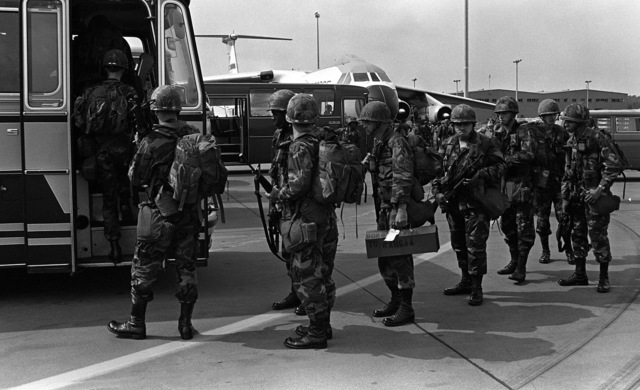 Members of the 1ST Infantry Division, from Fort Riley, Kansas, board buses after arriving aboard a C-141B Starlifter aircraft. Buses will move the troops to their prepositioning of material configured in unit sets (POMCUS) draw for supplies before continuing on to the marshalling area to participate in Exercise REFORGER `82