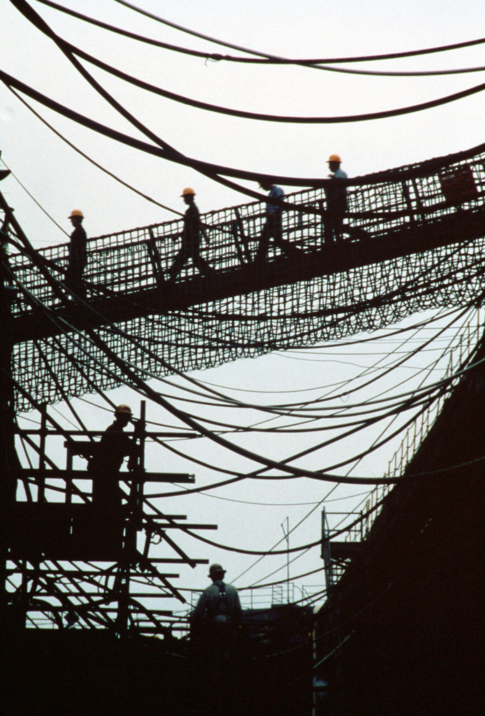 Shipyard workers cross the gangplank to the dry docked guided missile destroyer USS CLAUDE V. RICKETTS (DDG-5). They are silhouetted within a web of power line connected between the ship and the yard