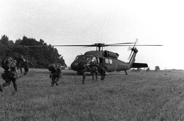 Soldiers of the Blue Forces who are participating in exercise Reforger-Carbine Fortress, head for a UH-60A Black Hawk (Blackhawk) helicopter to be airlifted out of their objective