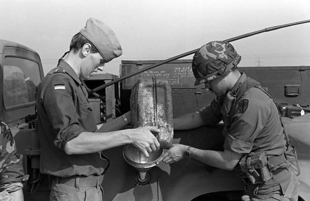 SPECIALIST 4 Angel Guerara, right, 66th Maintenance Company, helps a German soldier refuel a truck at a rest stop. The truck is part of a convoy en route to the exercise area for Carbine Fortress, a NATO exercise held annually in West Germany