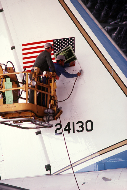 TECH. SGT. Ronald Collins, 89th Airlift Wing, removes a vertical stabilizer inspection panel from Air Force One, a VC-13B Stratoliner aircraft
