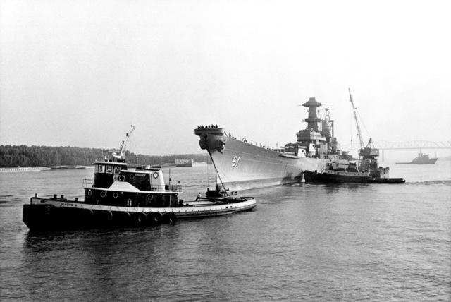 Tugs tow the battleship USS IOWA (BB 61) into Avondale Shipyards Inc. for modernization and reactivation