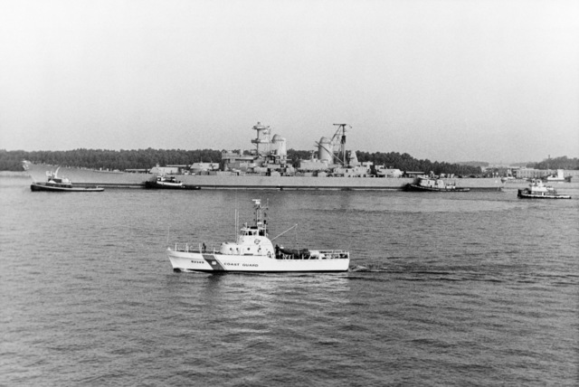 Tugs tow the battleship USS IOWA (BB 61) into Avondale Shipyards Inc. for modernization and reactivation. The U.S. Coast Guard patrol boat POINT SPENCER (WPB 82349) is in the foreground