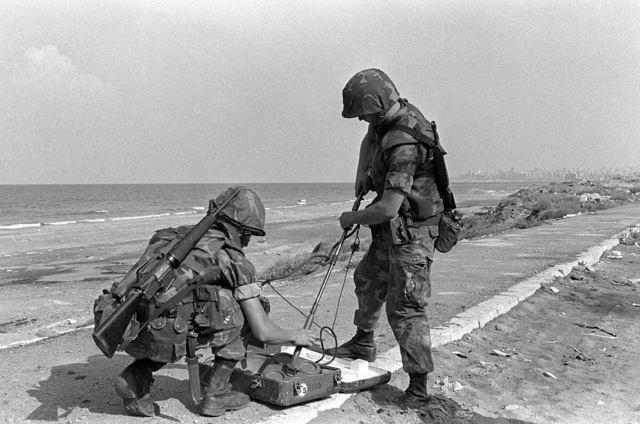 Two members of an explosive ordnance disposal team prepare to use a metal detector to check for mines on the beach. U.S. Marines have been assigned to Lebanon as part of a multinational peacekeeping force after a confrontation between Israeli forces and the Palestine Liberation Organization