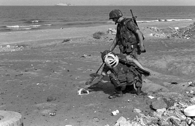 Two members of an explosive ordnance disposal team work together to mark the location of possible mines found with the aid of a metal detector on the beach. U.S. Marines have been assigned to Lebanon as part of a multinational peacekeeping force after a confrontation between Israeli forces and the Palestine Liberation Organization