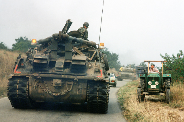U.S. Army M1 Abrams tanks join automobiles on a road through the German countryside, a farmer and tractor is off the road to make room for the giant tanks, during REFORGER '82, the multi-national military training exercise. Exact Date Shot Unknown