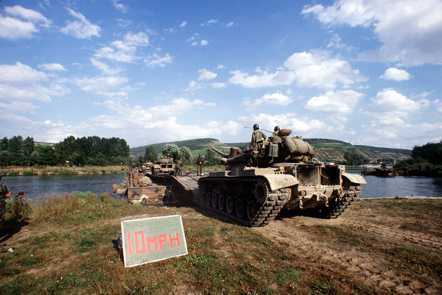 """U.S. Army M551 Sheridan tanks cross a river on a pontoon bridge, in foreground a sign advises """"10 MPH"""", during REFORGER '82, the multi-national military training exercise. Exact Date Shot Unknown"""
