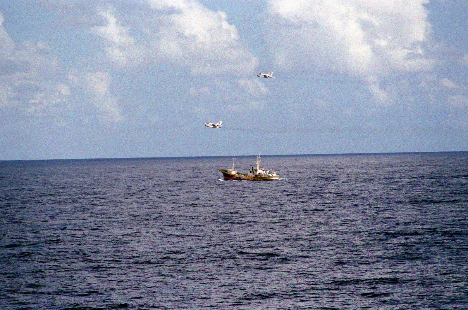 A view of the merchant vessel Mont Boron, suspected of drug smuggling off the Florida coast, as two Attack Squadron 205 (VA-205) A-7 Corsair II aircraft fly overhead as part of a drug interdiction operation. The photo was taken from the guided missile frigate USS CLIFTON SPRAGUE (FFG-16), which is providing a show of force as an example of the Navy's support to the vice president's South Florida Task Force