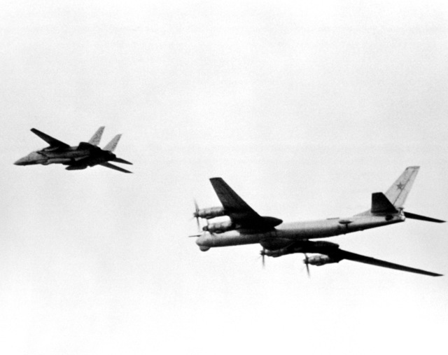 A left underside view of an F-14A Tomcat aircraft escorting a Soviet Tu-95 BEAR D reconnaissance aircraft away from the exercise Northern Wedding '82 task force. The Tomcat is from the aircraft carrier USS AMERICA (CV-66), not visible