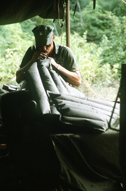A Navy seabee from Mobile Construction Battalion One, inflates his air mattress prior to taking a nap during Exercise Kennel Bear '4-82