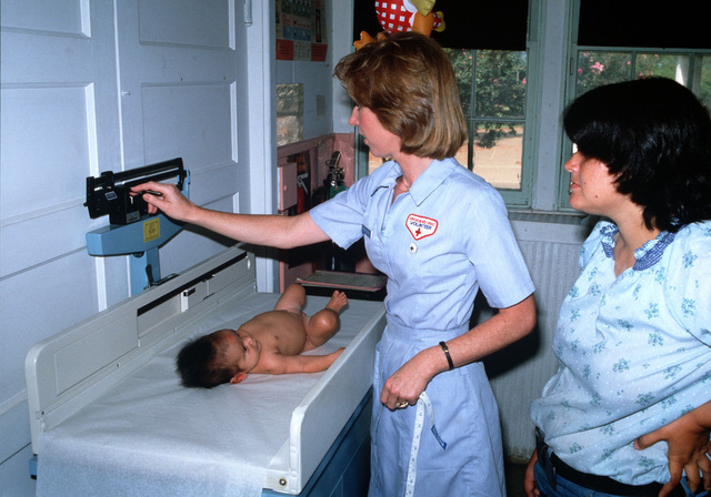 Bridget Corcoran, a Red Cross volunteer worker, weighs an infant at the Fort Polk Hospital Well-Baby Clinic
