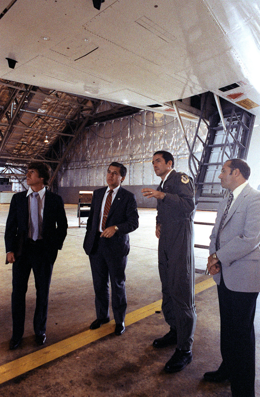 LCOL Leroy Schroeder, B-1 bomber chief test pilot, explains the features of the B-1 aircraft to Rep. Denny Smith, R-Oregon, center left, and two members of his staff. They are standing under the front of the aircraft, near the exit ladder