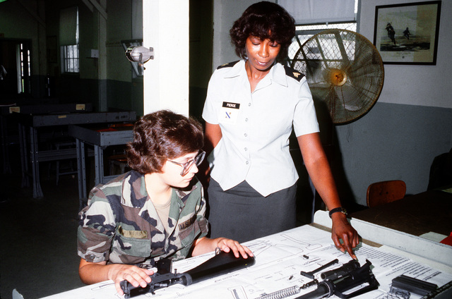 SGT. Bunda Pierce, instructor, and PVT. Debbie Berens discuss the layout of the M-16 rifle during the Military Occupation Specialty (MOS) 764 course at the Quartermaster School