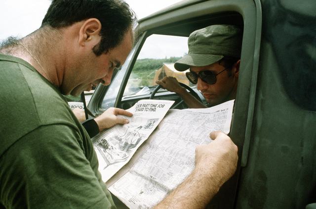 SSGT Jeffrey L. Robbins of the 374th Aerial Port Squadron reads a Stars and Stripes newspaper as A1C Rodney K. Haselden of the 374th Tactical Air Wing Combat Control Team, looks on during Exercise Kennel Bear '4-82