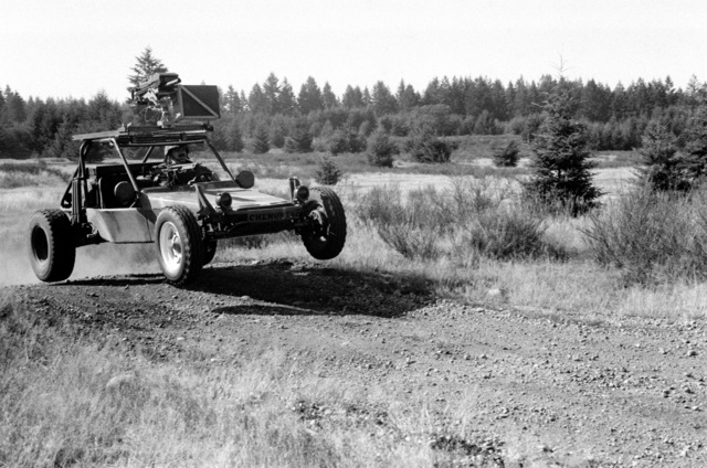 A left front view of a fast attack vehicle (FAV) prototype undergoing testing at the test driving range. The FAV is equipped with an M60 machine gun in front of the passengers seat and a Mark 19 Mod 3 40 mm automatic grenade launcher on the roll cage
