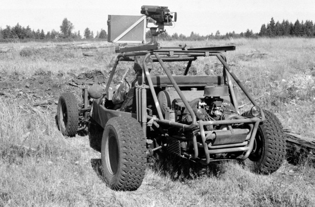 A left rear view of a fast attack vehicle (FAV) prototype parked on the test driving range. The FAV is equipped with an M60 machine gun in front of the passengers seat and a Mark 19 Mod 3 40 mm automatic grenade launcher on the roll cage