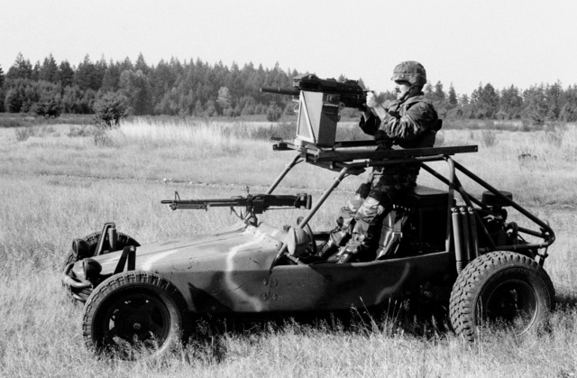 A left side view of a fast attack vehicle (FAV) prototype undergoing testing at the test driving range. The FAV is equipped with an M60 machine gun in front of the passengers seat and a Mark 19 Mod 3 40 mm automatic grenade launcher on the roll cage