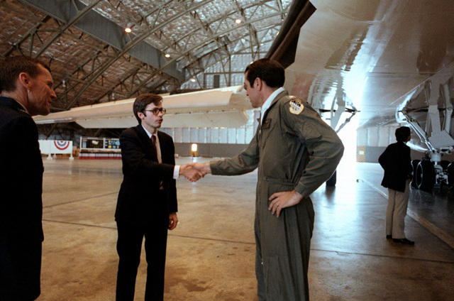 COL Jerry Miller, left, executive officer for MGEN Bill Thurman, and LCOL Leroy Schroeder, right, B-1 bomber chief test pilot; greet Tidal W. McCoy, assistant secretary of the Air Force, Manpower, Reserve Affairs and Installations. They are standing in front of a B-1 bomber on display in a hangar