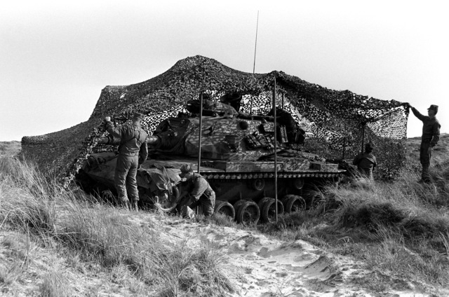 Members of the 4th Marine Amphibious Brigade cover their M-60A1 tank with camouflage netting during Operation Northern Wedding '82