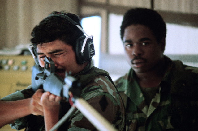 An instructor observes as a soldier takes an aim using the Weaponeer remedial rifle marksmanship trainer of the Fort Polk Training Aids Services Command. The trainer is mounted on a trailer that can be transported to rifle ranges or company areas to correct individual deficiencies in marksmanship