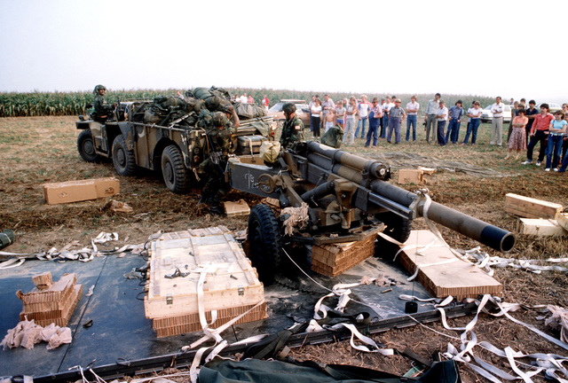 Members of the 82nd Airborne Division recover a 105mm howitzer after an air-drop from a C-141 Starlifter aircraft during Reforger '82. Local residents observe the operation
