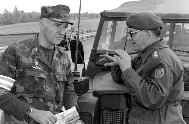 U.S. Marine Corps COL Fowler, umpire for Operation Northern Wedding '82, discusses the results of a tank battle with an umpire from the Danish army