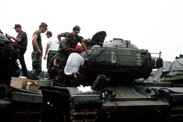 """Personnel assigned to the Training Aids Services Command MILES (Multiple Integrated Laser Engagement System) section instruct unit personnel in the application of Velcro to an """"M60 tank"""". The MILES system of training devices consist of laser engagement transmitters and detection systems for all the division`s direct-fire weapons"""
