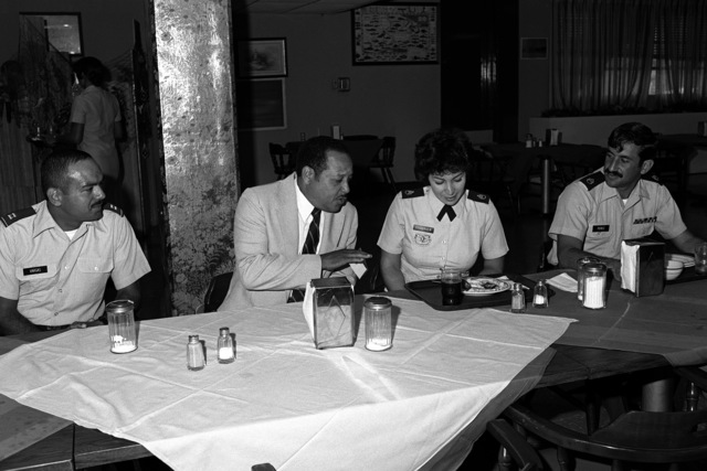 Deputy Under Secretary of the Army, John W. Shanon, joins SSGT Millie Chabrier, 758st U.S. Army Garrison, for a chat at the mess hall during his visit. Looking on are CPT E. Vargas (left) and SSGT Perez (right)