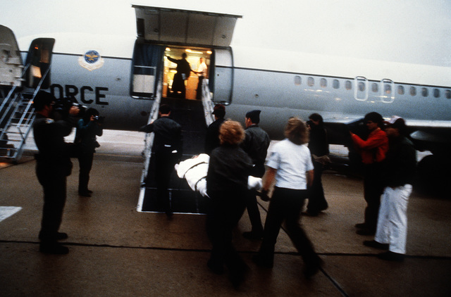 Injured survivors of a DC-10 passenger aircraft crash in Malaga, Spain, are carried aboard a waiting C-9 Nightingale aircraft from the Military Airlift Command, 73rd Aeromedical Airlift Squadron, for evacuation to Boston and Buffalo