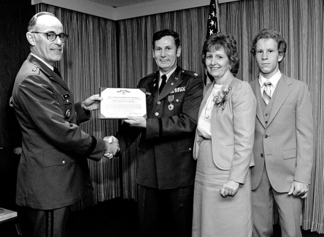 MGEN William E. Odom, deputy chief of staff for Intelligence, presents the Legion of Merit to LCOL Roger E. Miller. Attending the ceremony are LCOL Miller's wife Jeanne and son Douglas, at a ceremony the Pentagon