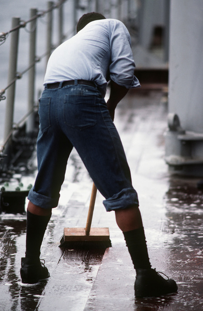 A crewman scrubs the deck of the battleship USS NEW JERSEY (BB 62). The NEW JERSEY, after recently completing renovation and modernization, is undergoing sea trials prior to reactivation in January 1983