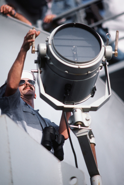 A signalman aboard the battleship USS NEW JERSEY (BB 62) uses the signal light to send a message to a nearby ship. The NEW JERSEY, after recently completing renovation and modernization, is undergoing sea trials prior to reactivation in January 1983