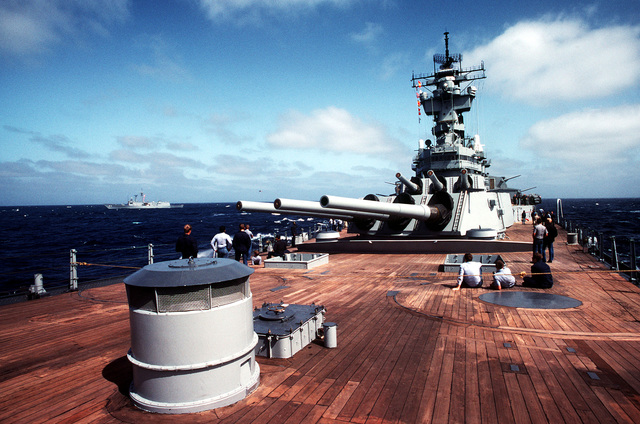 A view of the 16-inch/50-caliber guns on the forward deck of the battleship USS NEW JERSEY (BB 62). The guided missile frigate USS LEWIS B. PULLER (FFG-23) is cruising alongside. The NEW JERSEY, after recently completing renovation and modernization, is undergoing sea trials prior to reactivation in January 1983
