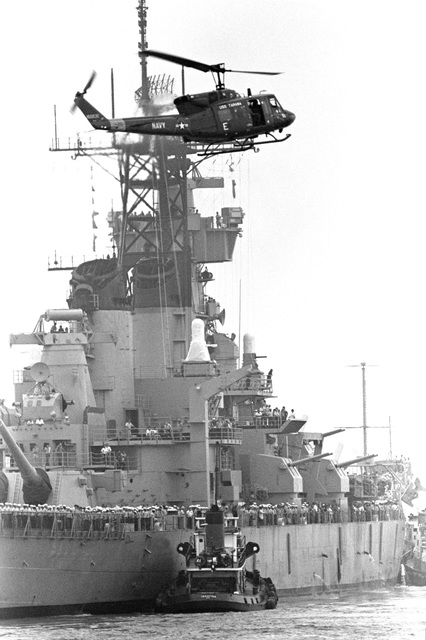 An UH-1 Iroquois helicopter flies near the battleship NEW JERSEY (BB-62) as it departs for sea trials
