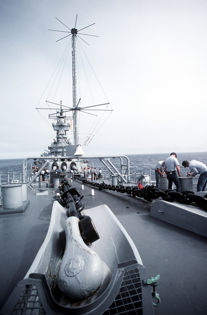 Anchor chains lay across the forward deck of the battleship USS NEW JERSEY (BB 62). Crewmen are chipping paint on the mooring bitts. The NEW JERSEY, after recently completing renovation and modernization, is undergoing sea trials prior to reactivation in January 1983