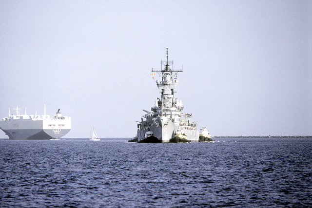 Bow view of the battleship USS NEW JERSEY (BB-62) being towed into the Pacific Ocean by tugboats for sea trials