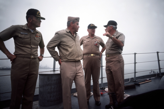 CAPT William M. Fogarty, commanding officer of the battleship USS NEW JERSEY (BB 62), second from right, and RADM Walter T. Piotti Jr., director, Surface Warfare Division, center, talk on the deck of the battleship. The NEW JERSEY, after recently completing renovation and modernization, is departing for sea trials prior to reactivation in January 1983