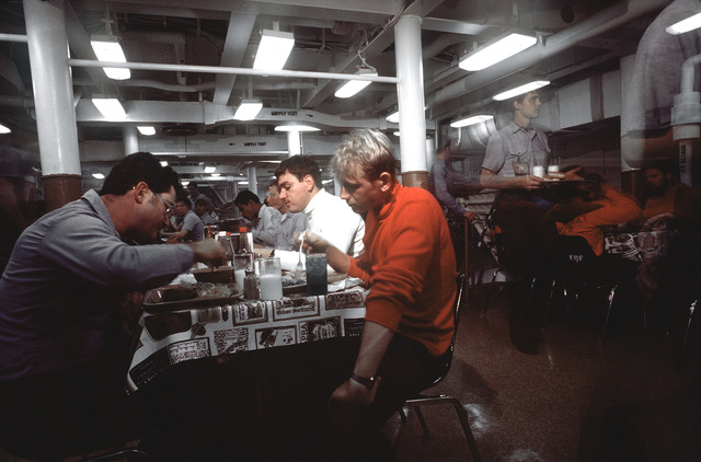 Crewmen eat in the dining area aboard the battleship USS NEW JERSEY (BB 62). The NEW JERSEY, after recently completing renovations, is on sea trials prior to its reactivation in January 1983