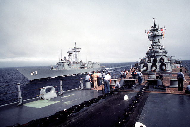 Crewmen on the forward deck of battleship USS NEW JERSEY (BB 62) watch as the guided missile frigate USS LEWIS B. PULLER (FFG 23) comes alongside. The NEW JERSEY, on sea trials after renovation and modernization, is scheduled to be reactivation in January 1983