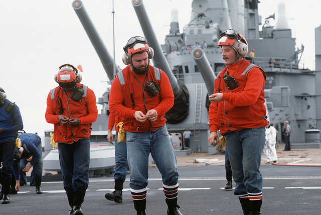 Crewmen police the deck, picking up debris, after the firing the 16-inch/50-caliber guns aboard the battleship USS NEW JERSEY (BB 62). The NEW JERSEY, after recently completing renovation and modernization, is undergoing sea trials prior to reactivation in January 1983