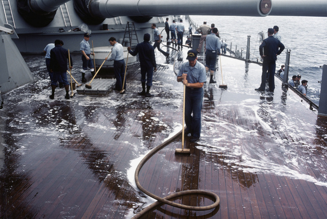 Crewmen scrub the deck aboard the battleship USS NEW JERSEY (BB 62). The NEW JERSEY, after recently completing renovation and modernization, is undergoing sea trials prior to reactivation in January 1983