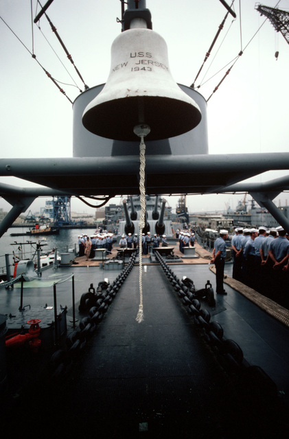 Crewmen stand in formation on the forward deck of the battleship USS NEW JERSEY (BB 62). The ship's bell hangs in the foreground. The NEW JERSEY, after recently completing renovation and modernization, is departing for sea trials prior to reactivation in January 1983