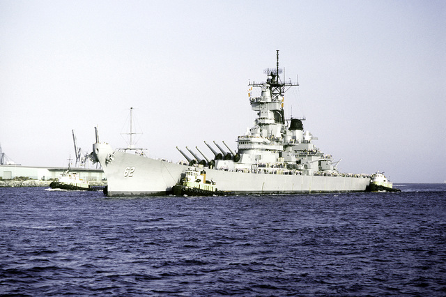 Port bow view of the battleship USS NEW JERSEY (BB-62) being towed from the dock by tugboats for sea trials