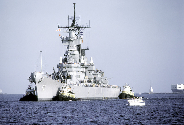 Port bow view of the battleship USS NEW JERSEY (BB-62) being towed into the Pacific Ocean by tugboats for sea trials