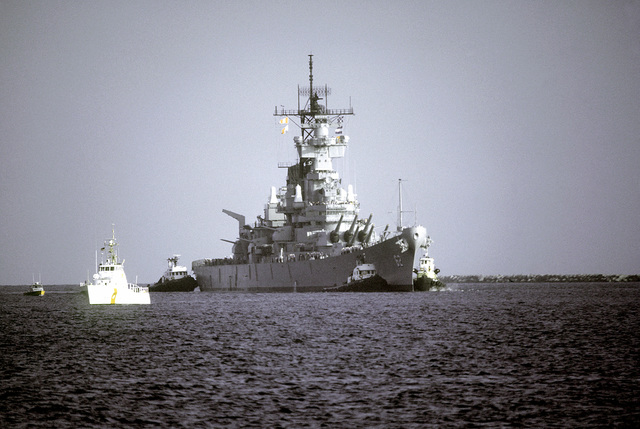 Starboard bow view of the battleship USS NEW JERSEY (BB-62) being towed from the dock by tugboats for sea trials