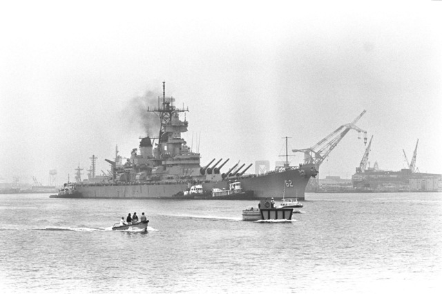 Starboard view of the battleship NEW JERSEY (BB-62) being maneuvered away from the pier by tug boats as it departs for sea trials