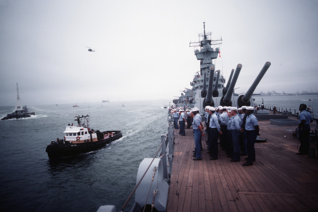 The crew stands in formation on the deck of the battleship USS NEW JERSEY (BB 62) as the ship departs for sea trials. The NEW JERSEY, after undergoing renovation and modernization, is scheduled to be reactivated in January 1983